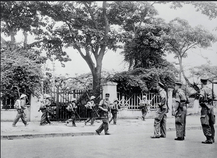 20 May 1955, Haiphong, Indochina --- As Haiphong Came Under New Management. Haiphong, Indochina A French patrol stands at left, ready to move off, as Communist Vietminh troops move in to