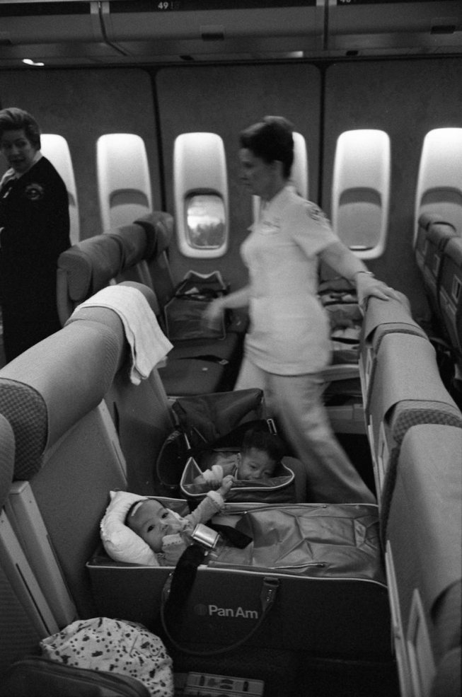 1975, April 5 – Aircraft at San Francisco International Airport – San Francisco, CA – Nurses, Refugee Children, Others – children buckled into seats on plane; nurses moving in the background; all not in frame – Vacation Trip to California - Arrival of Operation Babylift Plane from South Vietnam; Vietnam Refugee - San Francisco, California
