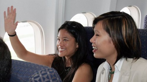 007Wendy Greene, left, returns the wave to ground workers in Atlanta as Tiana Mykkeltvedt looks on as they begin their return journey to Vietnam from Atlanta on board a World Airways jet
